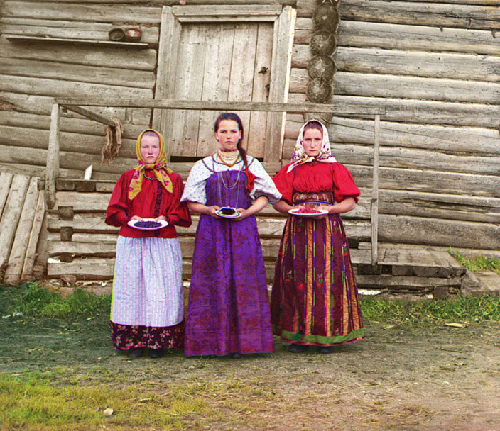 Peasant Girls - Three young women offer berries to visitors to their izba, a traditional wooden house, in a rural area along the Sheksna River, near the town of Kirillov. Photograph by Sergei Prokudin-Gorsky